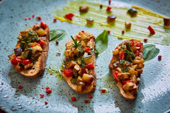 Vegan food: bruschetta with bell pepper, tomatoes, arugula, thyme and basil Royalty Free Stock Photo