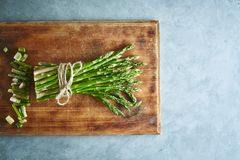 Bunch of asparagus on wooden cutting board Stock Photos