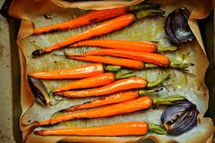 Vegan food with carrots and onion grilled in the oven Royalty Free Stock Photos