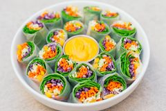Vegan food concept. Tasty green spring rolls made of rice paper and spinach, filled with fresh chopped vegetables. Small plate stock images