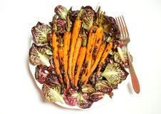 Vegan food with grilled carrots and bitter salad Stock Photos