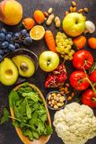Vegan food ingredients on a dark background. Vegetables, fruits, cereals, nuts, beans top view.