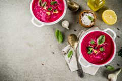 Vegan food, summer cold Beetroot gazpacho soup with lemon, avocado and fresh herbs copy space top view stock photo