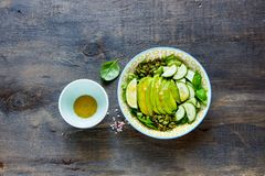Vegan green salad. Vegan green summer salad with avocado, arugula, cucumbers and pumpkin seeds and dressing in bowl over wooden background. Top view, flat lay Royalty Free Stock Image