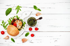 Vegan grilled eggplant, arugula, sprouts and pesto sauce burger. Top view, overhead, flat lay. Copy space. Royalty Free Stock Image