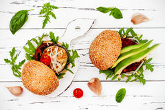 Vegan grilled eggplant, arugula, sprouts and pesto sauce burger. Veggie beet and quinoa burger with avocado. Top view, overhead Stock Image