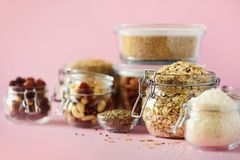 Vegan health food over pink background with copy space. Nuts, seeds, cereals, grains in glass jars. Antioxidants, omega 3, protein royalty free stock image
