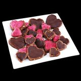 Vegan heart-shaped cookies. Vegan raw-food heart-shaped cookies served on a square plate isolated on black background Royalty Free Stock Image