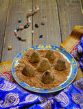 Vegan Homemade Candies in cocoa powder on Ethnic background. Vegan Homemade Candies in cocoa powder on Ethnic background Stock Image