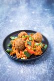 Vegan Jambalaya Recipe. Side view of vegan jambalaya and exotic rice dish. Falafels on top of rice on a dark small plate and a grey background. Cooked falafel stock photography