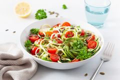 Vegan ketogenic spiralized courgette salad with avocado tomato pumpkin seeds royalty free stock photos