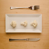 Vegan low-carb diet raw cauliflower on rectangular plate. Concept of vegan and vegetarian low-carb diet. A single raw cauliflower on a square rectangle plate Royalty Free Stock Photos