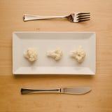 Vegan low-carb diet raw cauliflower on rectangular plate Royalty Free Stock Photos
