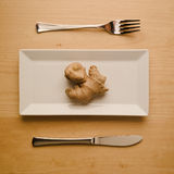Vegan low-carb diet raw ginger root on rectangular plate. Concept of vegan and vegetarian low-carb diet. A single raw and uncut ginger root on a square rectangle Royalty Free Stock Images