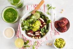 Vegan lunch flat lay. Green vegetable vegan salad with beets meatballs, Guacamole and tahini dressing. Healthy vegetarian food co. Green vegetable vegan salad stock photo
