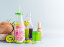 Vegan matcha fusion drink in bottle with ingredients: matcha, red berries juice, kiwi fruits and coconut milk on table with copy royalty free stock image