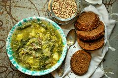 Vegan meal: quinoa soup with organic cabbage and potatoes. Vegan food : quinoa soup with organic cabbage and potatoes with whole wheat bread on a vintage table Stock Images