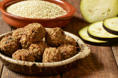 Vegan meatballs on a wooden table. Some vegan meatballs in an earthenware plate on a rustic wooden table, with some vegetables in the background stock photos