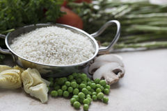 Vegan Paella Ingredients. Rice, artichokes, peas, mushrooms and other ingredients for vegetarian paella Stock Image