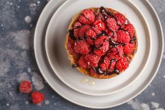 Homemade pancakes with raspberries on a gray plate, dark backgro. Vegan pancakes with raspberries and chia seeds on a gray plate, dark background, top view Stock Photo