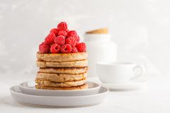 Vegan pancakes with raspberries and chia seeds on white plate, w. Vegan pancakes with raspberries and chia seeds on a white plate, white background. Healthy Royalty Free Stock Image