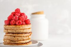 Vegan pancakes with raspberries and chia seeds on white plate, w. Vegan pancakes with raspberries and chia seeds on a white plate, white background. Healthy Stock Photography