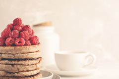 Vegan pancakes with raspberries and chia seeds on white plate, w. Vegan pancakes with raspberries and chia seeds on a white plate, white background. Healthy Stock Image
