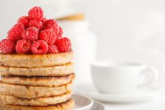 Vegan pancakes with raspberries and chia seeds on white plate, w. Vegan pancakes with raspberries and chia seeds on a white plate, white background. Healthy Royalty Free Stock Images