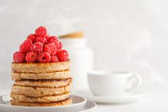 Vegan pancakes with raspberries and chia seeds on white plate, w. Vegan pancakes with raspberries and chia seeds on a white plate, white background. Healthy Royalty Free Stock Photography