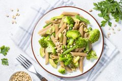 Vegan pasta penne with broccoli, avocado and pine nuts top view. royalty free stock image
