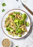 Vegan pasta penne with broccoli, avocado and pine nuts top view. royalty free stock photo