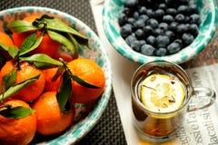 Vegan, petit déjeuner cru avec le thé vert, mandarines et myrtilles Photographie stock libre de droits