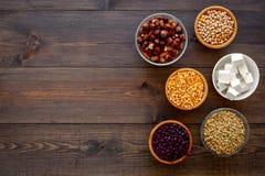 Vegan protein source. Legumes, nuts, cheese. Raw beans, chickpeas, lentil, almond, hazelnut on dark wooden background stock photos