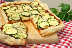 Vegan puff pastry pizza. With zucchini and mashed tomatoes, garlic, oregano and basilicum Royalty Free Stock Photography