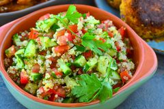 Vegan quinoa salad served in earthen bowl. With fresh cucumber,tomato,onions,mint and parsely stock photo