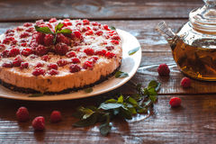 Vegan raspberry cake and green tee. Appetizing vegetarian pie from protein jelly with fresh berries of raspberry and a teapot with green tea. Healthy food Stock Image