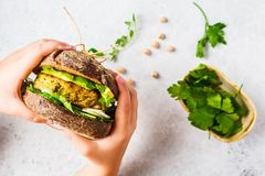 Vegan sandwich with chickpea patty, avocado, cucumber and greens in rye bread in children`s hands royalty free stock photography