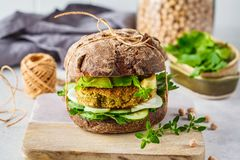 Vegan sandwich with chickpea patty, avocado, cucumber and greens in rye bread stock image