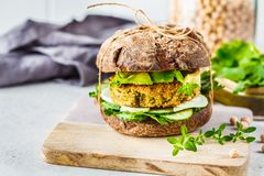 Vegan sandwich with chickpea patty, avocado, cucumber and greens in rye bread royalty free stock photos