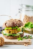 Vegan sandwich with chickpea patty, avocado, cucumber and greens in rye bread stock photos