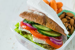Vegan sandwich in lunch box with carrots and nuts Stock Image