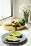 Vegan sandwich, rye bread toast, avocado, whole & halved, vegenaise sauce. Toasted sourdough, eggless mayonnaise, wood slice, daff. Odil flower vase. National stock image