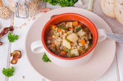 Vegan soup with pearl barley, vegetables and mushrooms stock photo