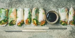 Vegan spring rice paper rolls over concrete background, wide composition. Helathy Asian cuisine. Flat-lay of vegan spring rice paper rolls with vegetables, soy Stock Images