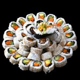 Vegan sushi on a big plate. Vegan raw-food sushi served on a big plate isolated on black background Royalty Free Stock Images