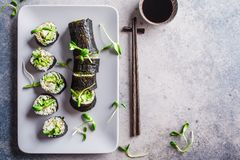 Vegan sushi rolls with avocado, brown rice, cucumber, tofu and seedlings on gray background, copy space. Plant based diet concept