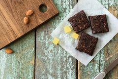 Vegan sweets. Delicious homemade almond brownies and fruit jelly. Cubes on shabby rustic wooden background top view copyspace Stock Photography