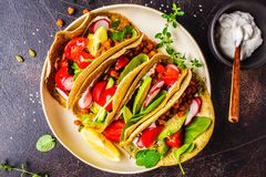 Vegan tacos with baked chickpeas, avocado, sauce and vegetables on dark background, top view