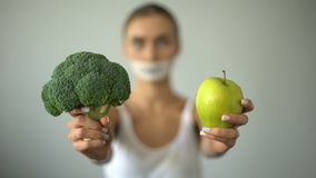 Vegan with taped mouth holds vegetables, concept of severe diet, harm to health