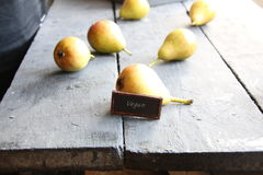 Vegan text and Juicy flavorful pears. Vintage composition. Juicy flavorful pears on a wooden table and vegan text Stock Photo